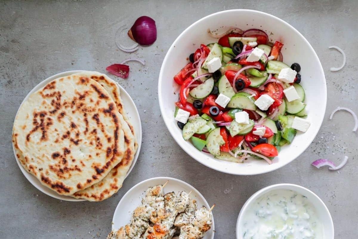 griekse salade met pitabroodjes, kip souvlaki en tzatziki op een grijze achtergrond