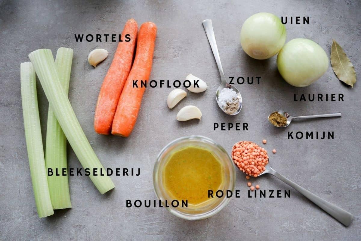 Alle ingrediënten voor vegan linzensoep op een grijze achtergrond