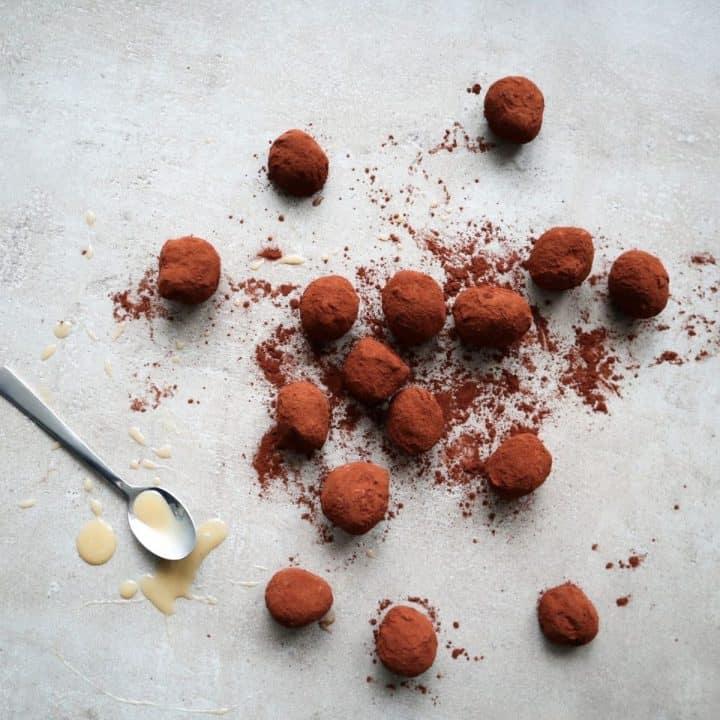 Chocolade karamel truffels op een grijze achterrond en een lepel